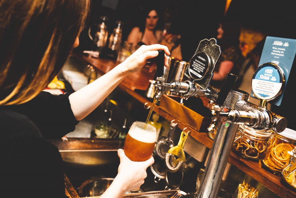 A bartender filling a glass with tap beer