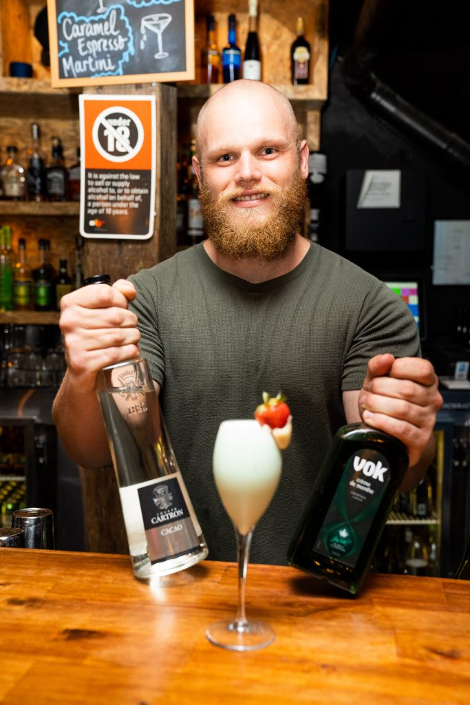 A bartender showing two different alcoholic bottles and a cocktail