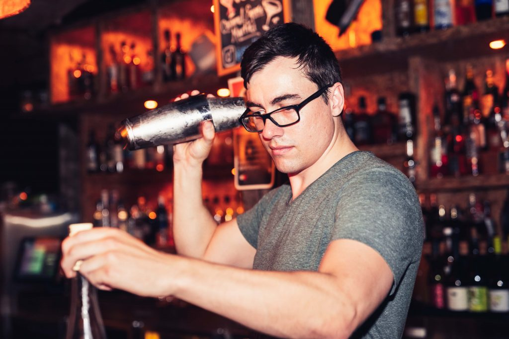 A male bartender mixing drinks