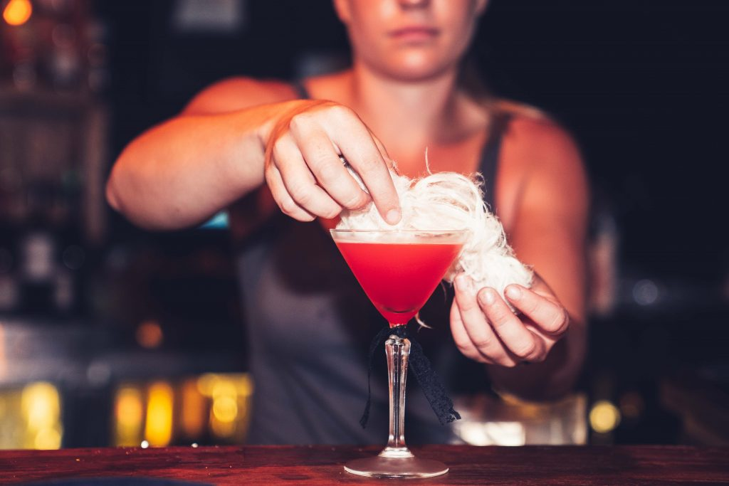 A female bartender adding finishing touches to a cocktail