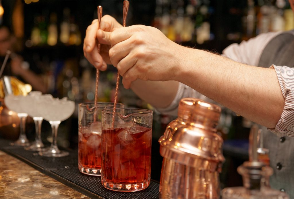 A male bartender stirring cocktails on the glass with a stirrer
