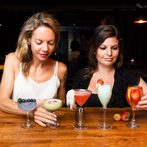 Two women enjoying five different cocktails