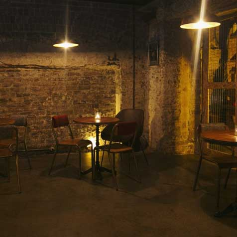 Underground restaurant with dimly lit dining space with cement flooring and stone walls