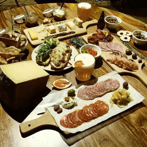 A table-full of charcuterie grazing board with condiments and nibbles, wine and a glasses of beer