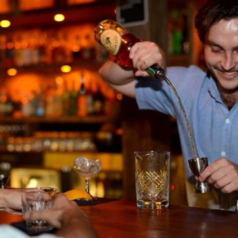A bartender pouring drinks for his customer