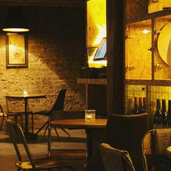 Dimly lit underground restaurant dining space with a wine display cabinet